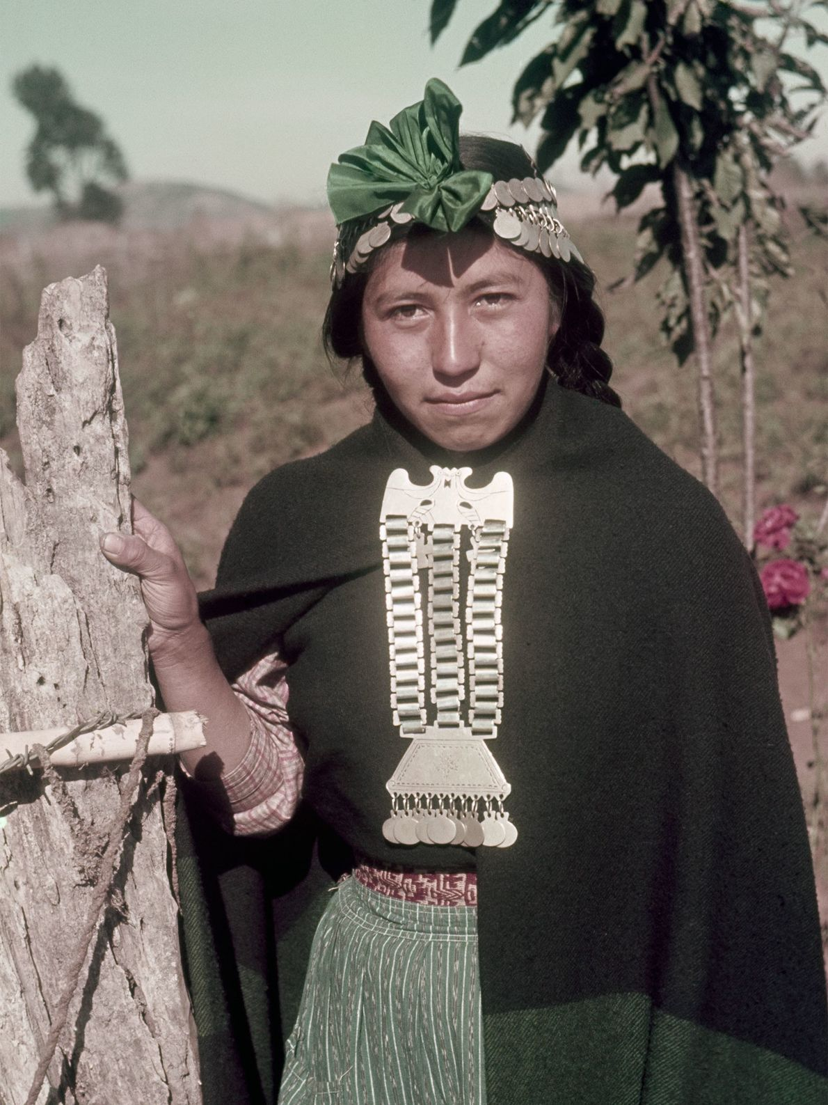 An Araucanian woman from Chile wears elaborate silver pieces as jewelry and headpiece adornments.