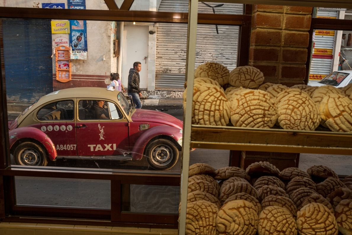 Picture of loaves of bread in a bakery window, with a red taxi seen in the ...