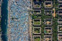 A slum lines the Mithi River near the National Stock Exchange in Mumbai. The city is ...