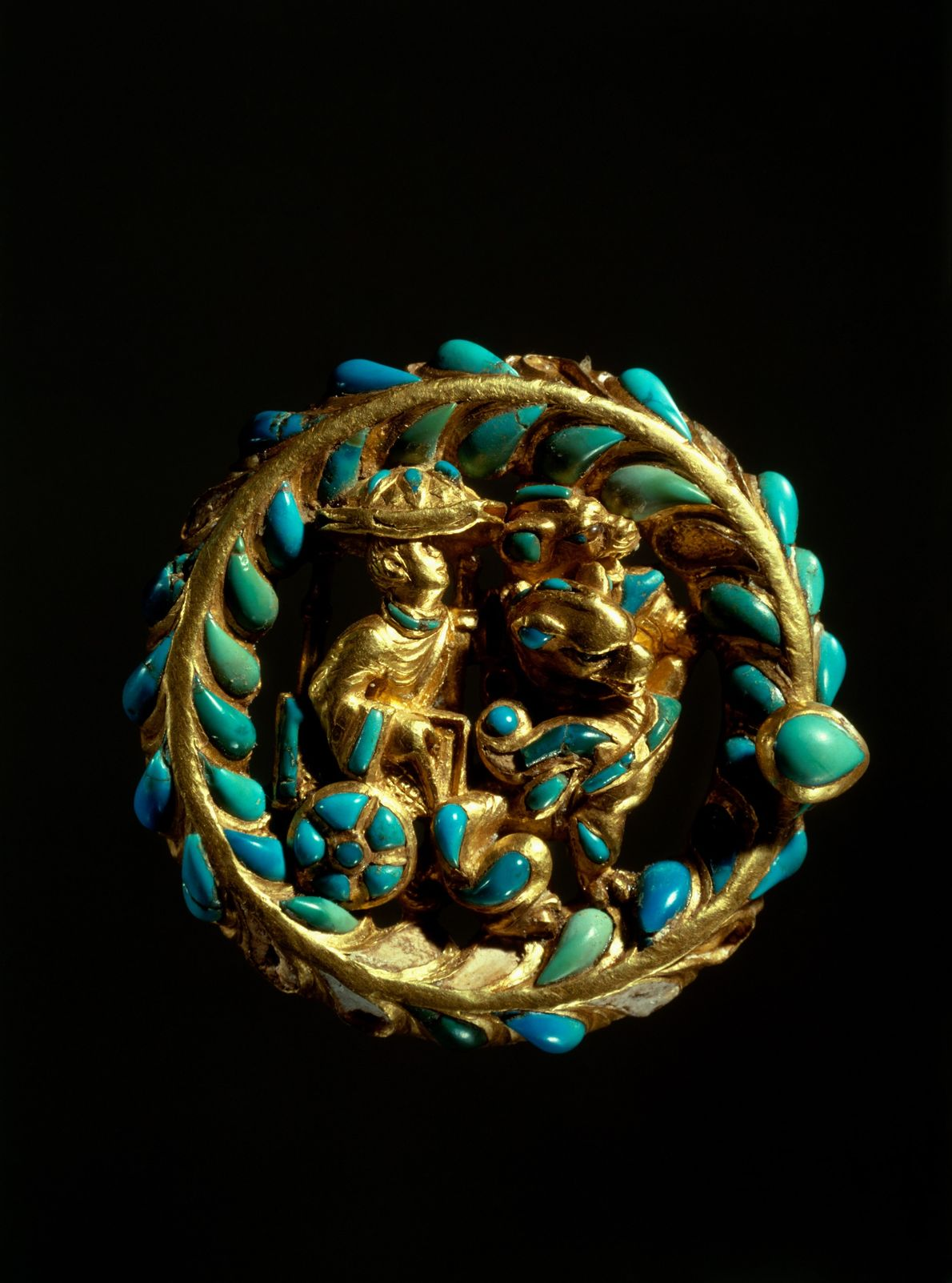 This turquoise-studded buckle bears images from the East, charioteers driving Chinese-style canopied chariots. But the winged ...