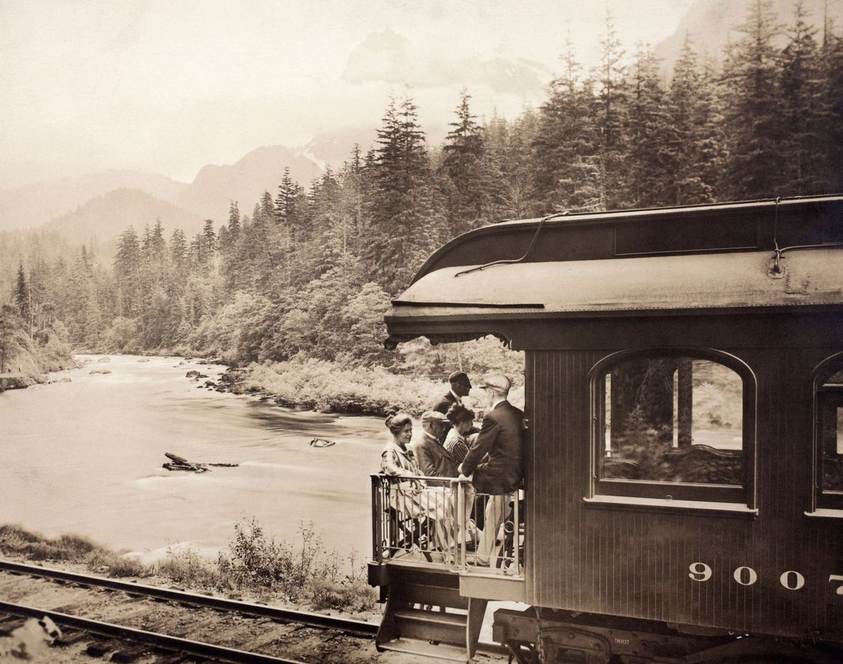 In Skykomish County, Washington, passengers on the Oriental Limited train peer down while rolling across a …