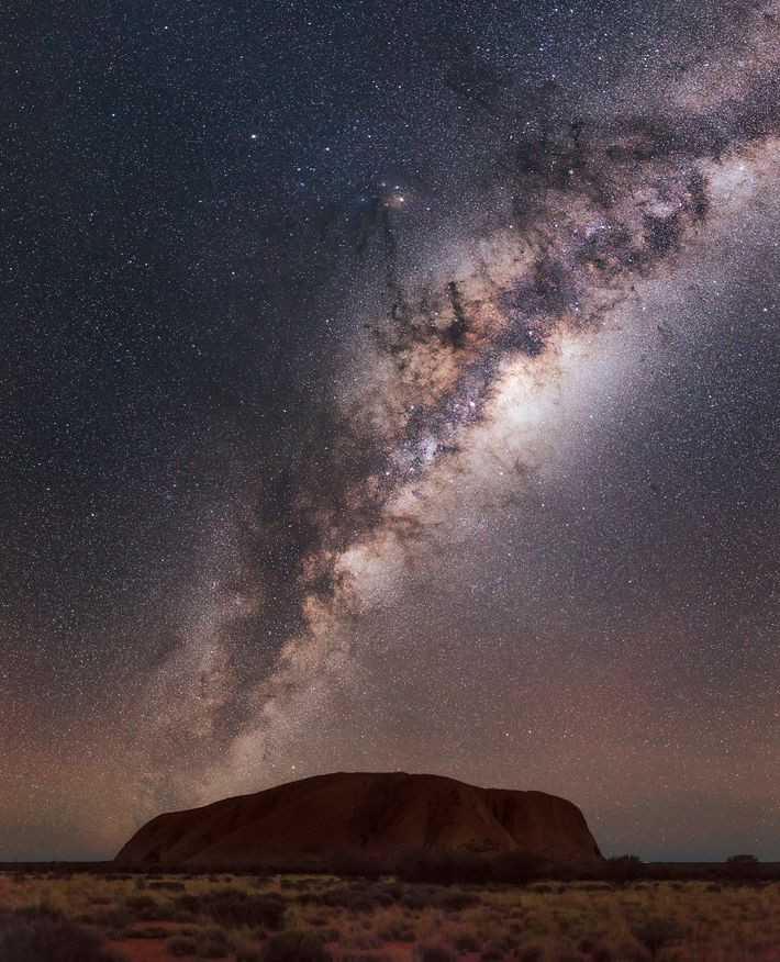 The Milky Way arches over Uluru.