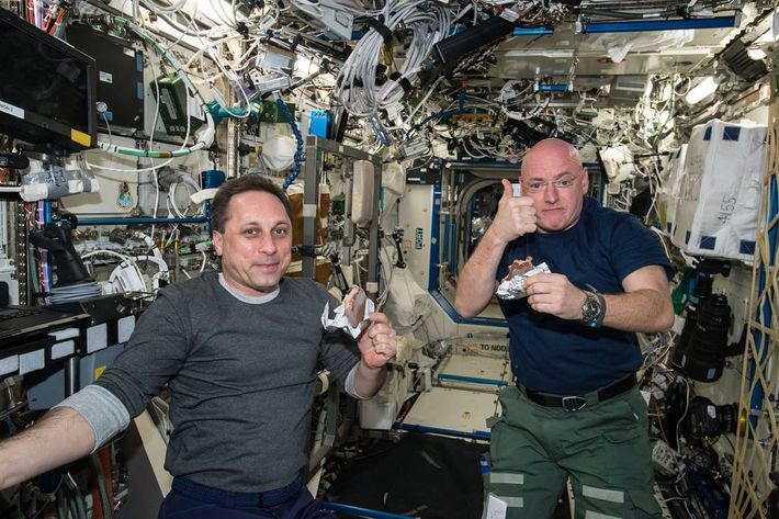NASA astronaut Scott Kelly gives the thumbs up for the quality of his space food snack ...