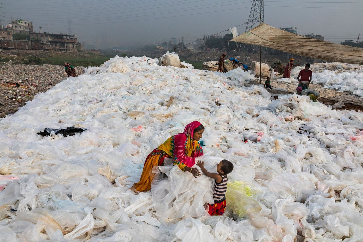 After sheets of clear plastic trash have been washed in the Buriganga River, a woman spreads ...