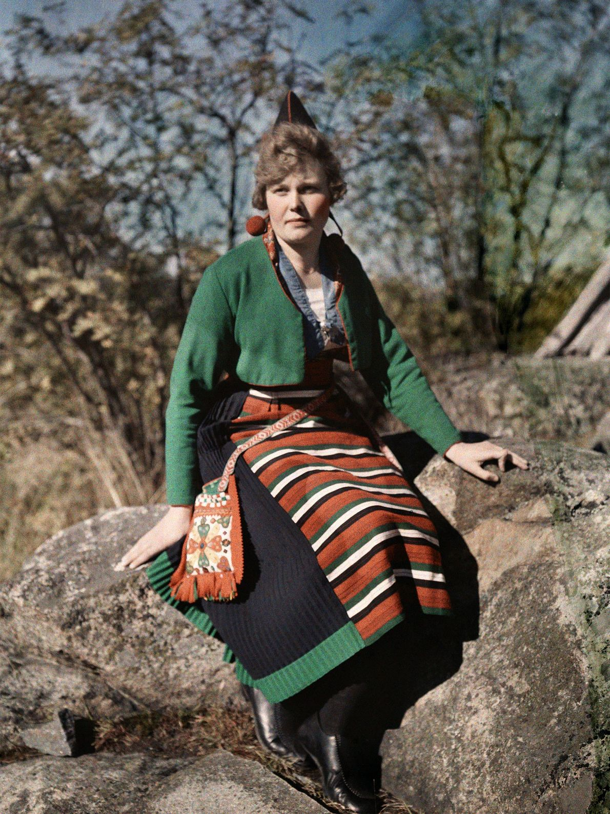 A woman from Rattvik, Sweden, poses on a boulder in the woods while wearing a pointed ...
