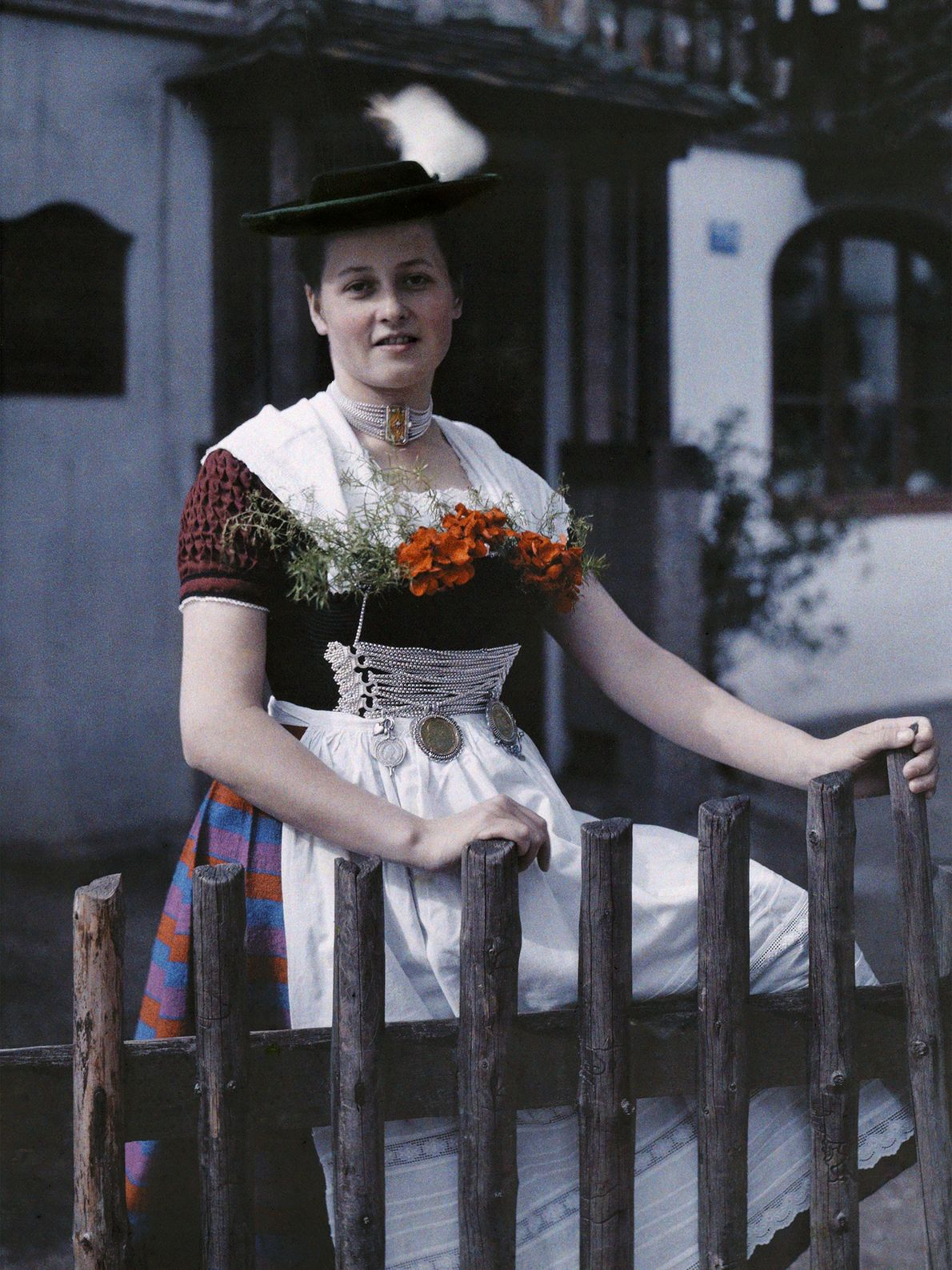 A Bavarian woman poses by a fence near her house in Germany wearing a nearly flat ...