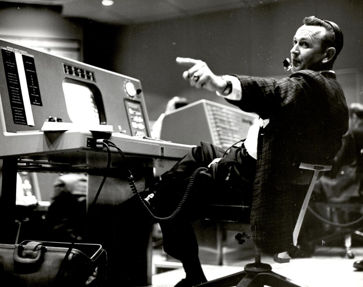 Christopher Kraft, flight director during Project Mercury, works at his console inside the Flight Control area ...