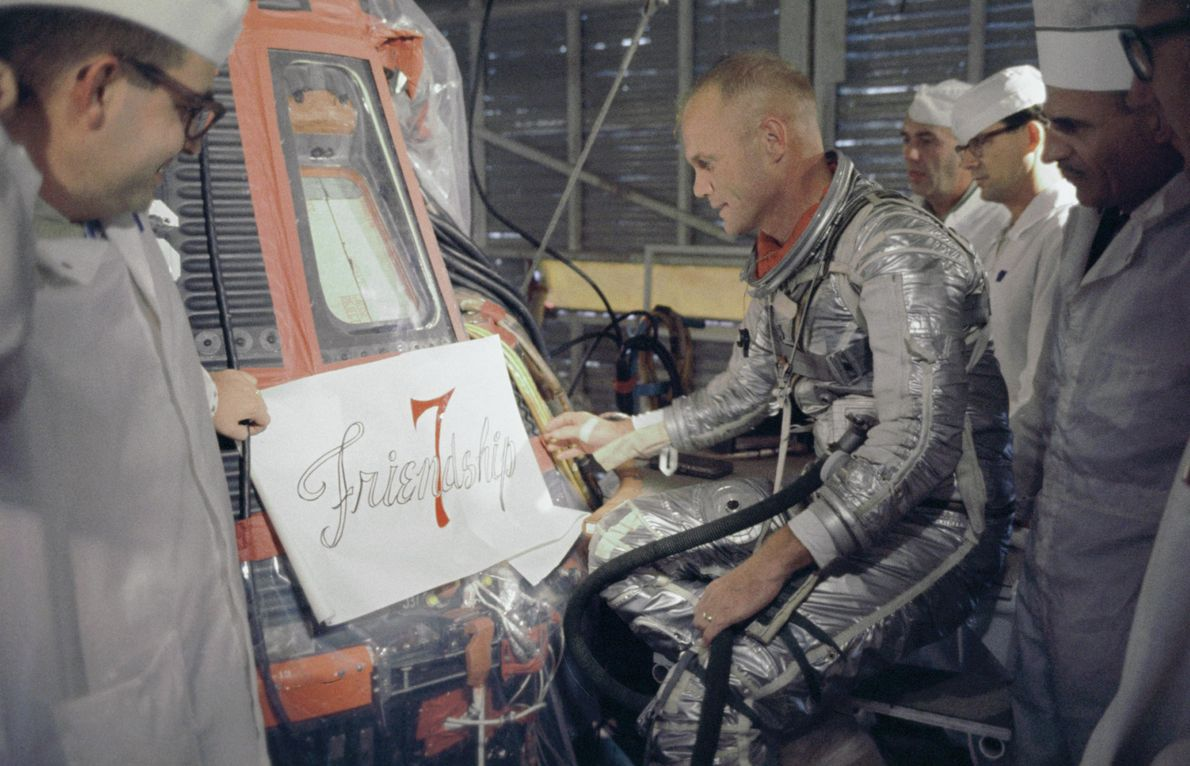 Astronaut John Glenn examines the logo for the name 'Friendship 7' to be painted on the outside ...