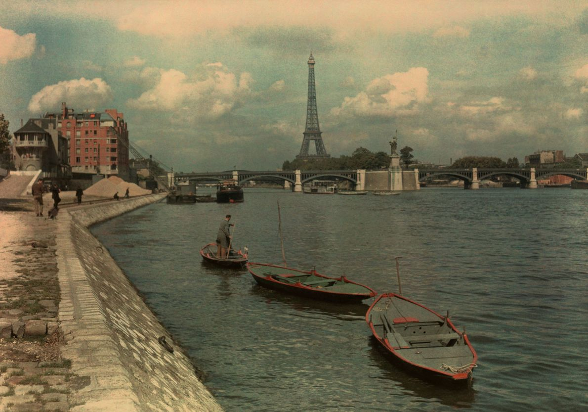 Boats in a chain float down the Seine River toward the Eiffel Tower.