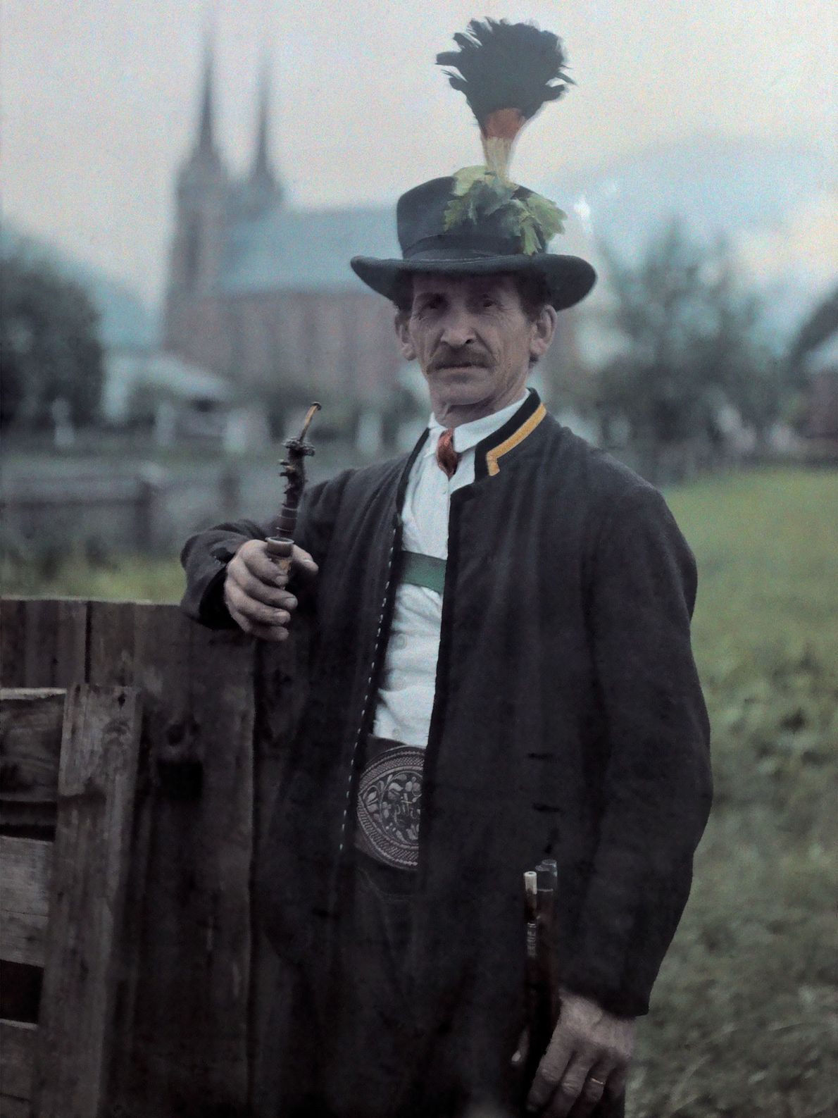 A man in a guard uniform and hat poses with his pipe in Austria.