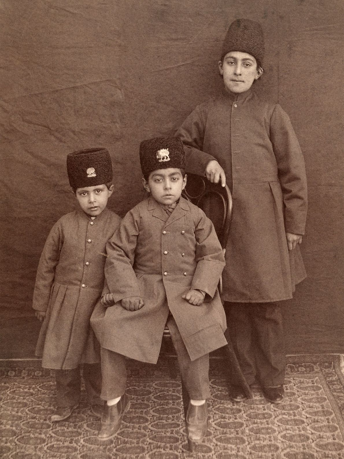 Three Persian boys pose for a portrait in their traditional clothing and hats.