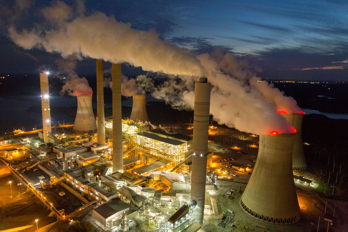 Steam and smoke rise from the cooling towers and chimneys of a power plant in Juliette, ...