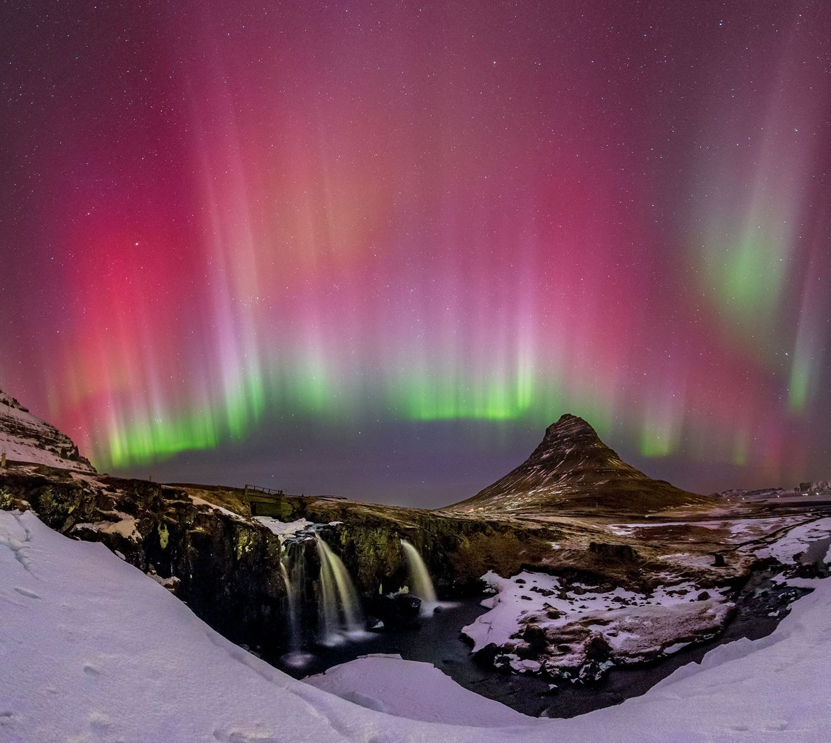A night view of a waterfall and icicles in Iceland, accented by the northern lights.
