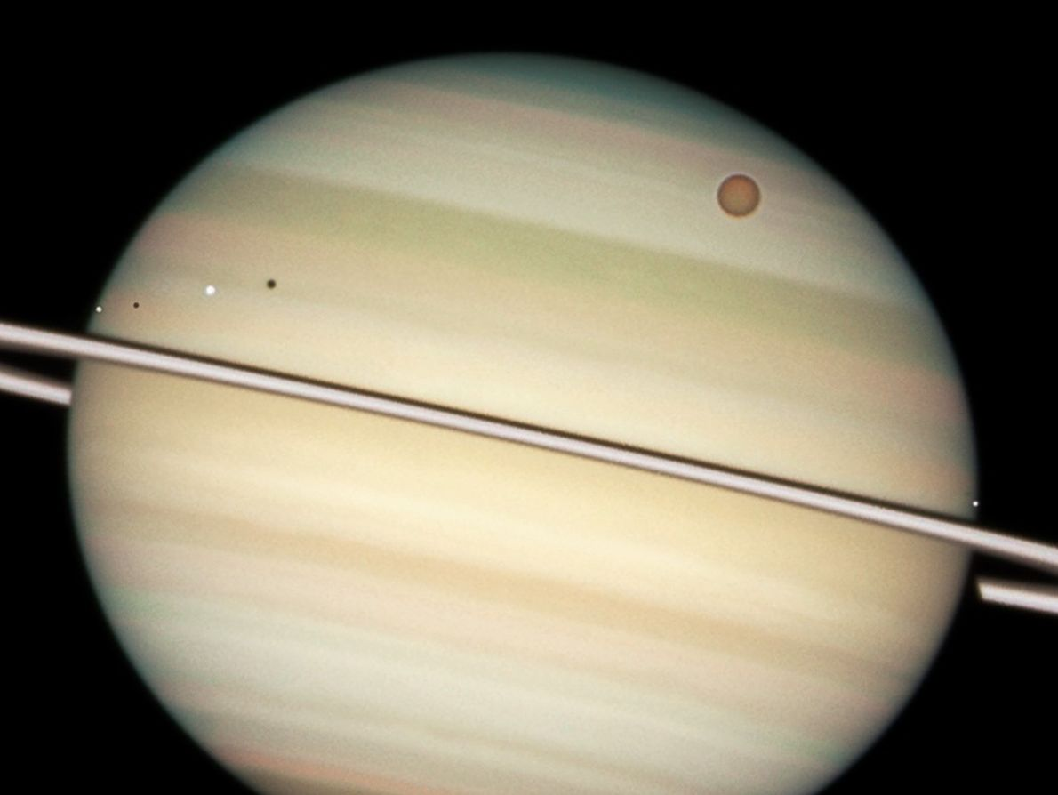 Planet Saturn, along with several of its moons, poses for a Hubble close-up in this 2009 ...