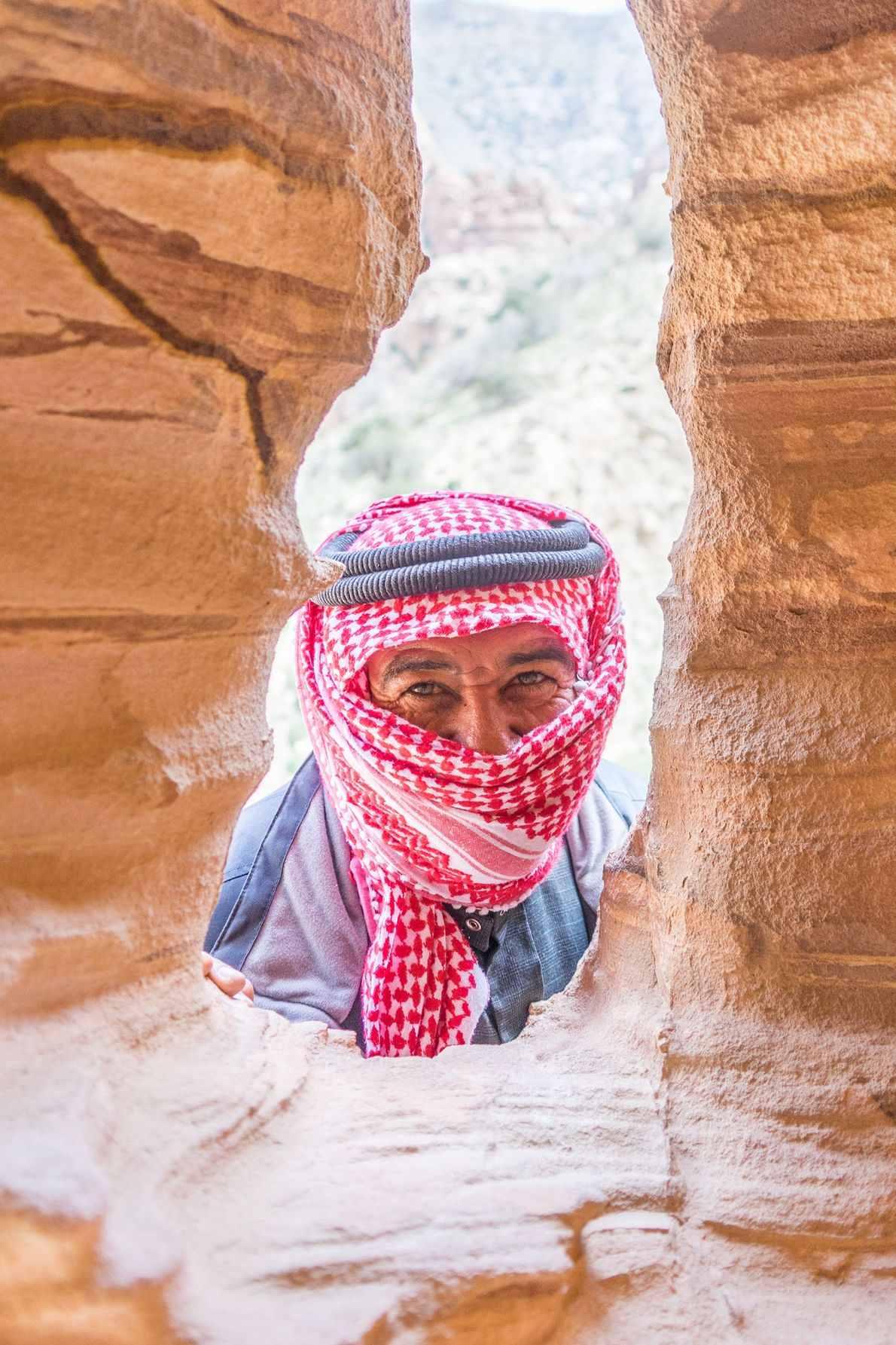 A covered face emerges between rocks.