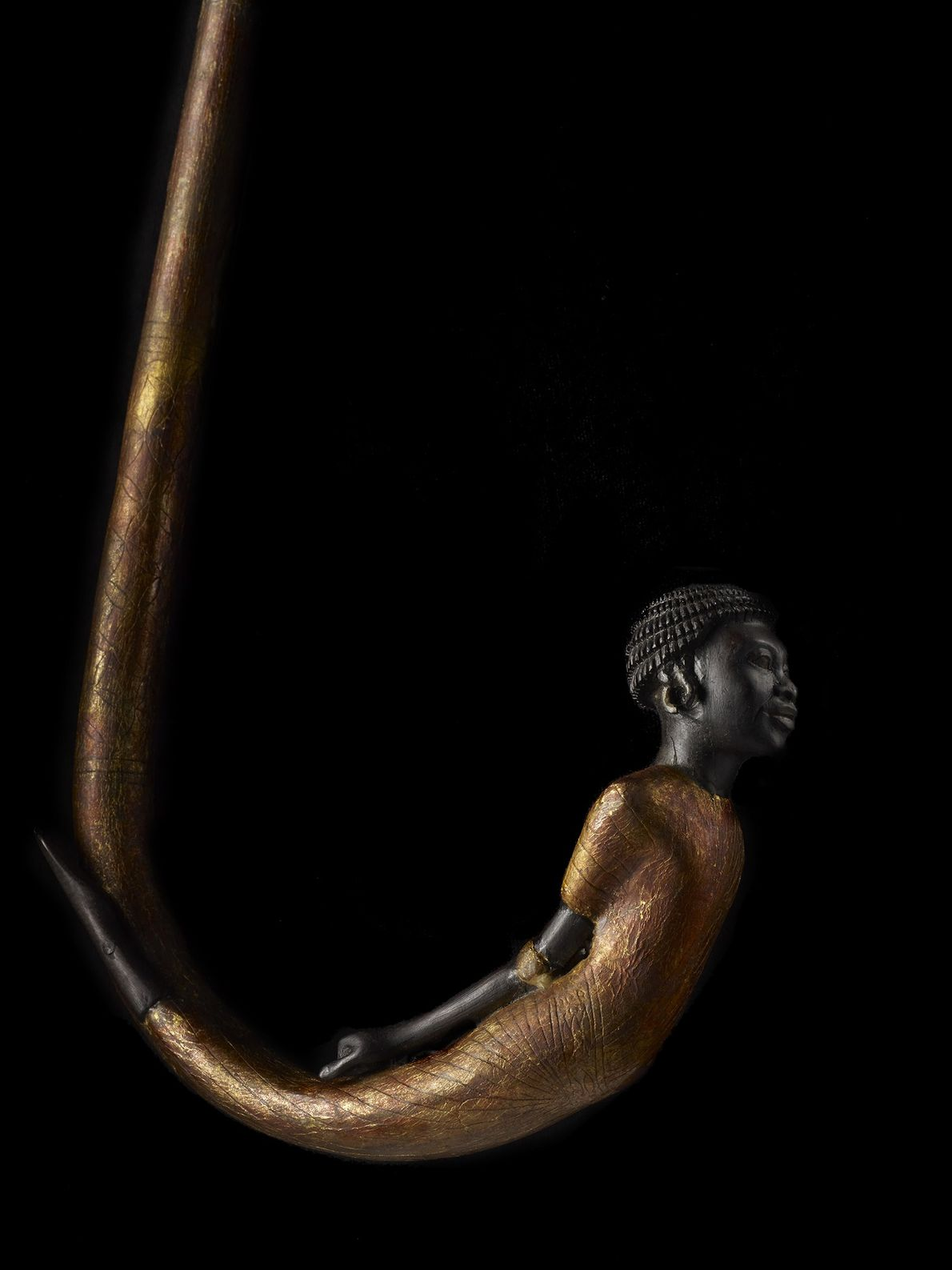 A carving of a Nubian captive adorns the handle of a walking stick recovered from the …