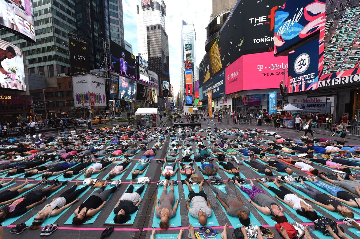 People take part in the 15th annual Times Square yoga event celebrating the Summer Solstice, the ...
