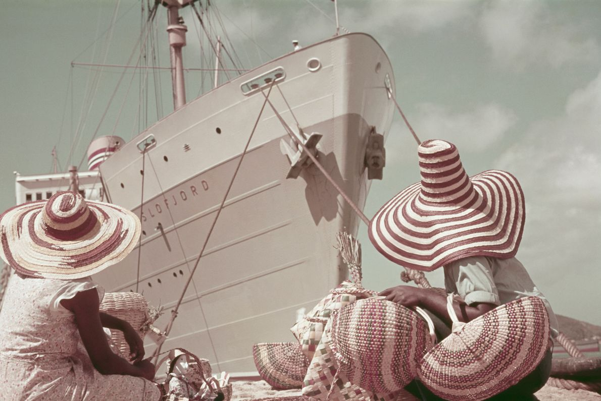 Vendors welcome a steamer ship of tourists to the island.