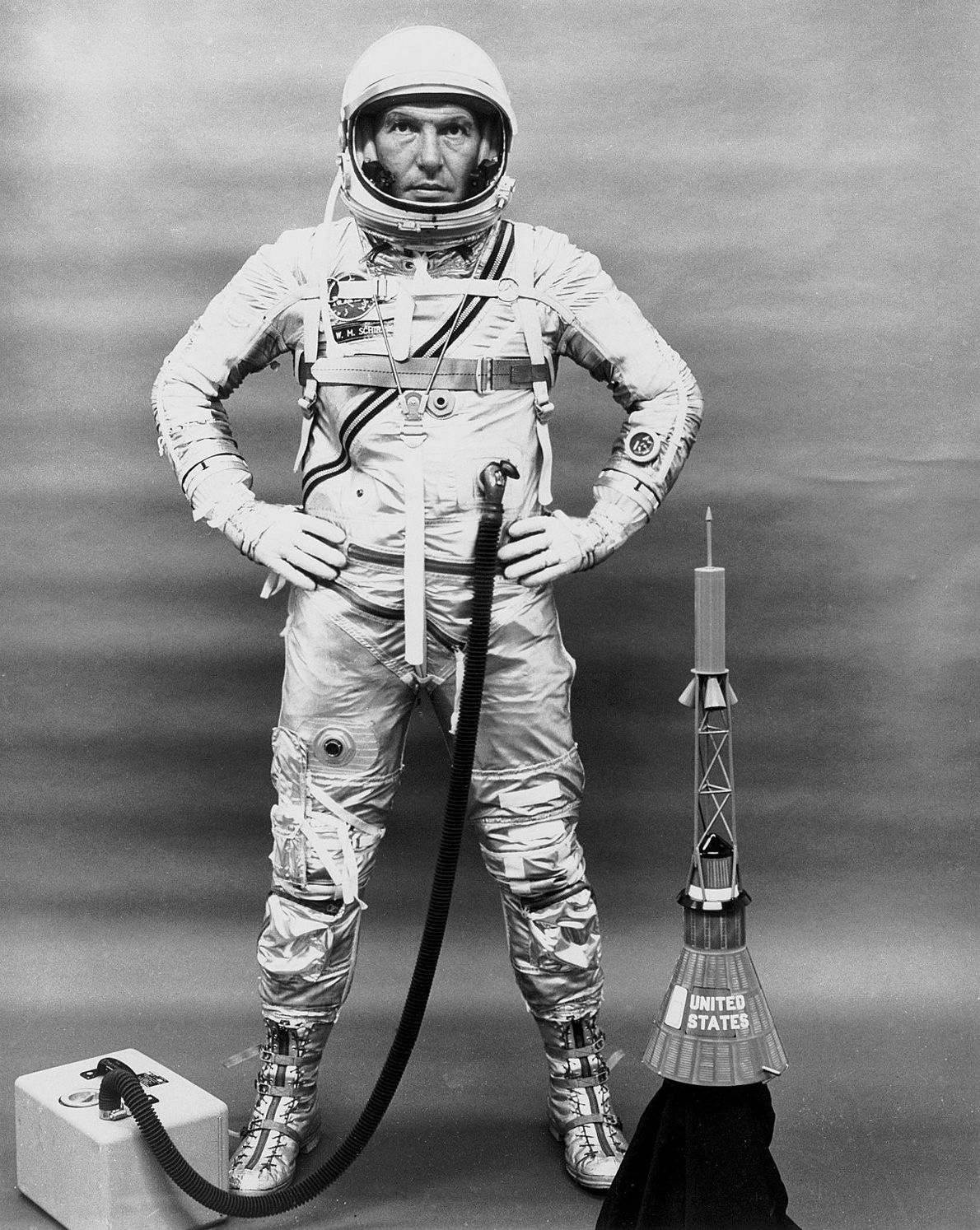 Wally Schirra poses with his suit, portable oxygen kit and a model of the Mercury capsule. ...