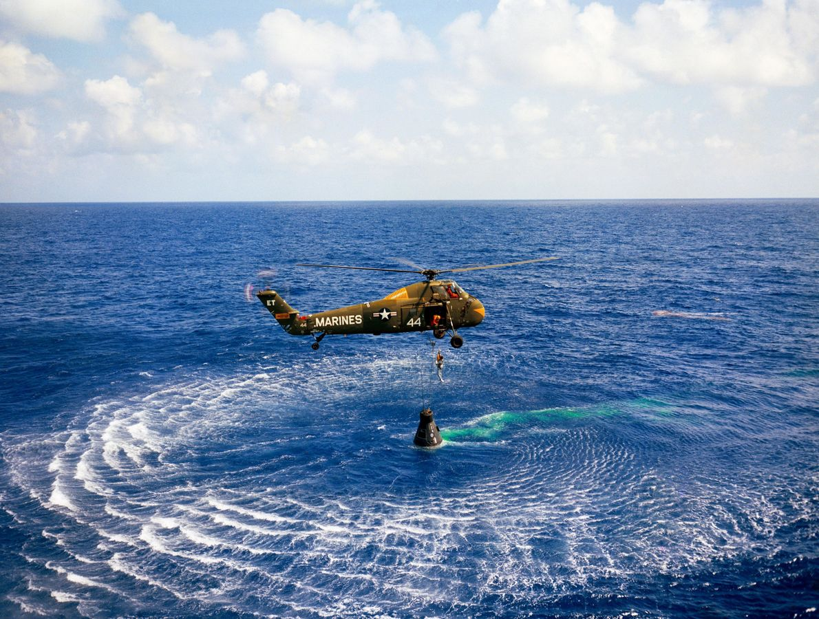 Alan Shepard and his Mercury capsule are collected by military helicopter after splashdown in the Atlantic, ...