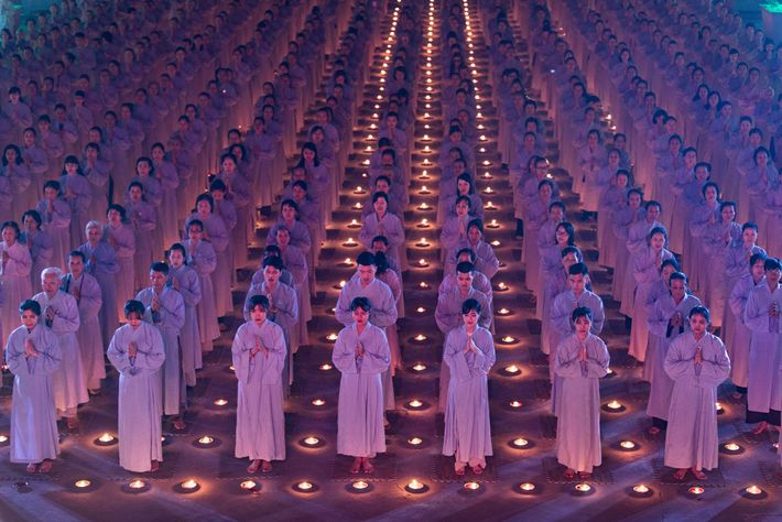 """""""Hundreds of Buddhist pray in the night of flower garlands and coloured lanterns on the birthday ..."""