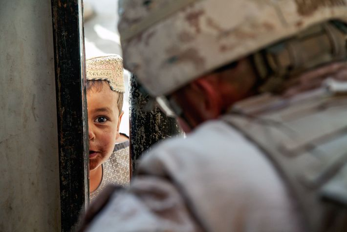 """""""An Afghan child interacts with Marine Cpl. J.W. Morris through a checkpoint barrier at forward operating ..."""