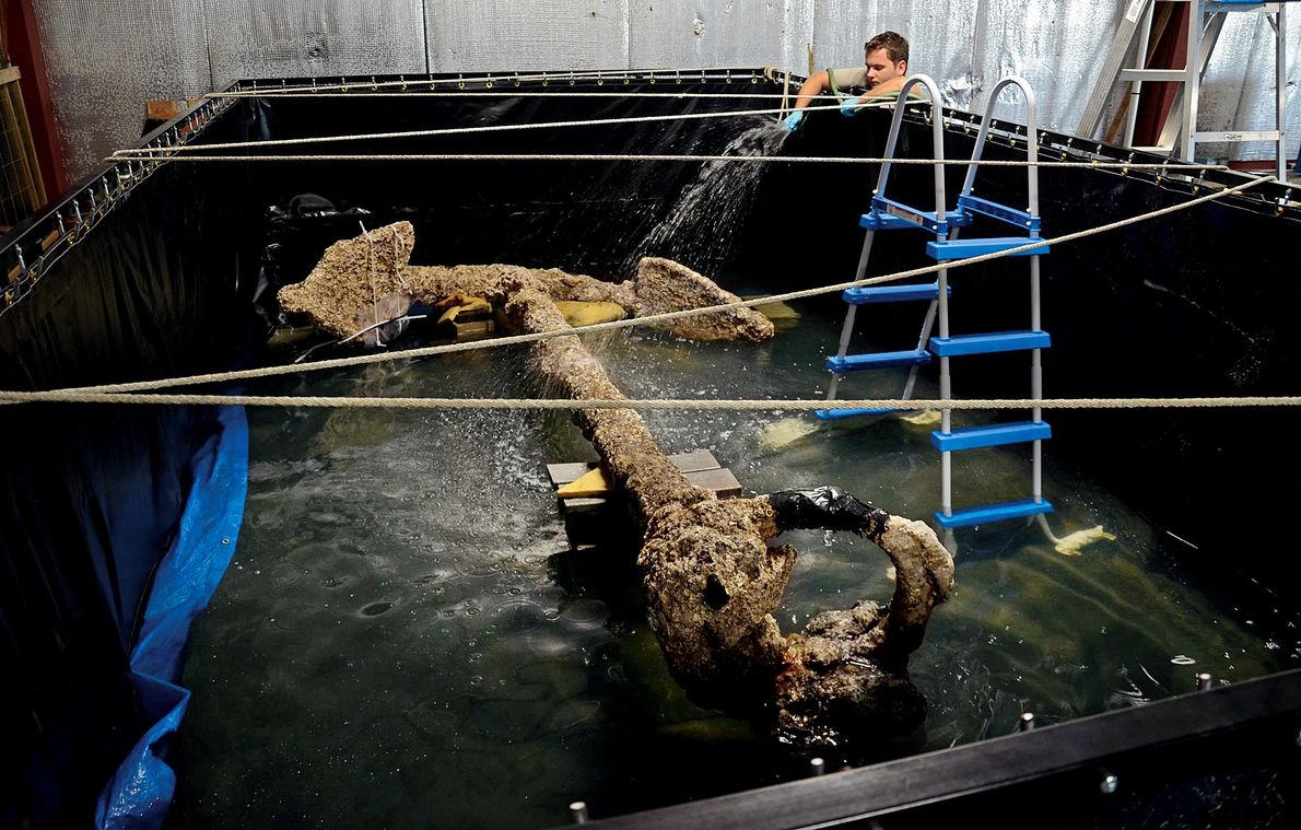 A conservator sprays water on an anchor from Queen Anne's Revenge to keep it wet while ...