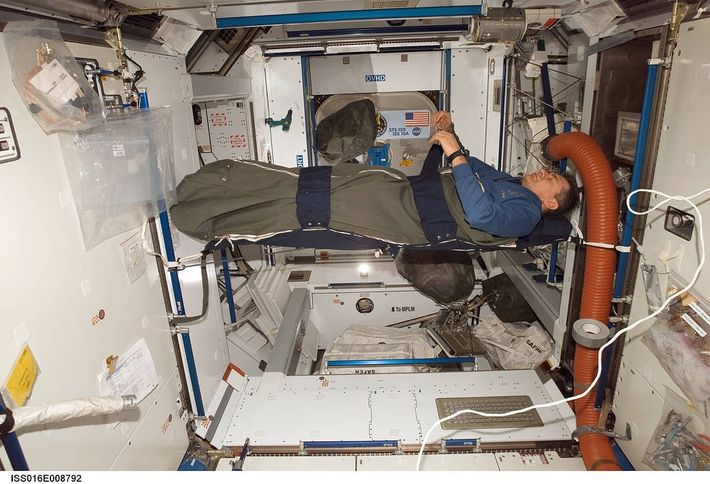 European Space Agency astronaut Paolo Nespolirests in his sleeping bag in the Harmony node of the ...