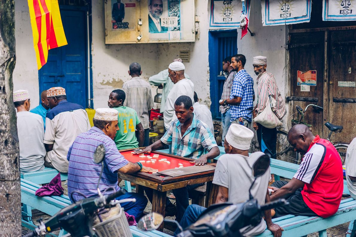 In one of Stone Town's small squares, men gather to play dominoes