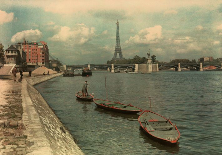 The Seine slips beneath the Pont Grenelle near the Eiffel Tower, shown here in July 1936.