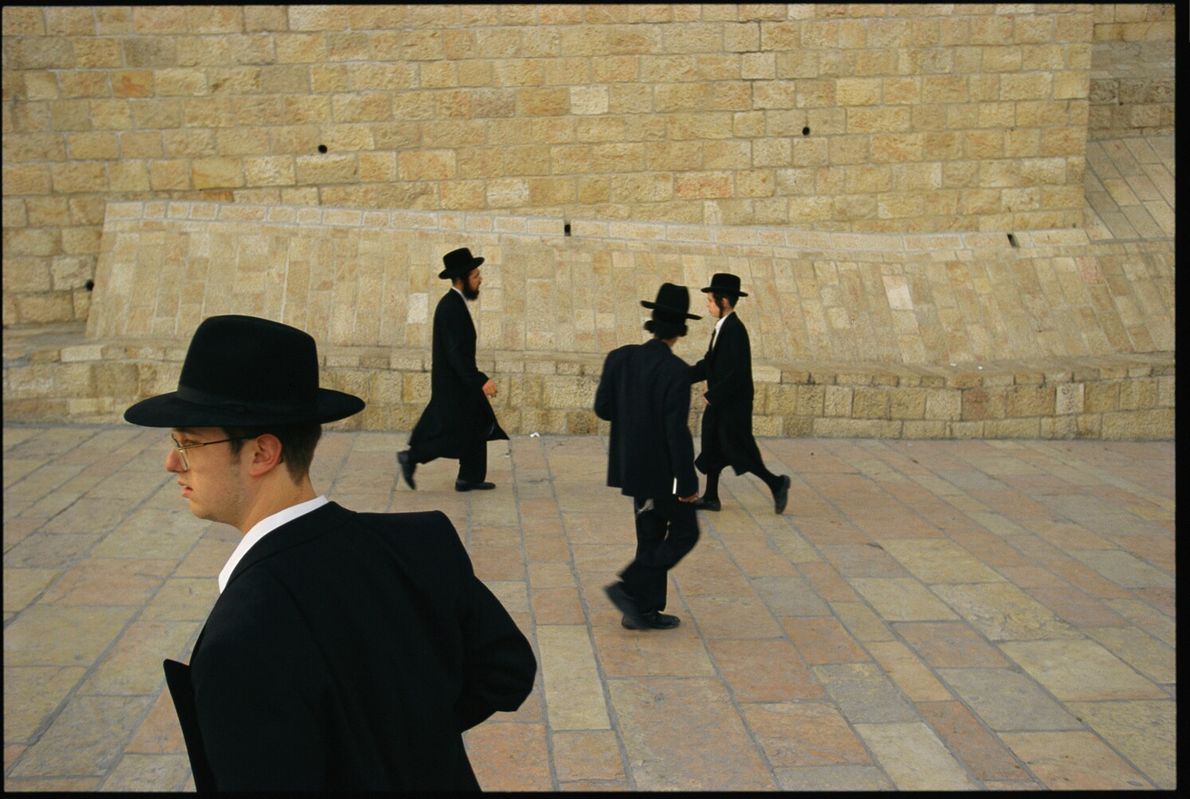 Picture of four Orthodox Jewish men in traditional garb walking past the Western Wall in Jerusalem
