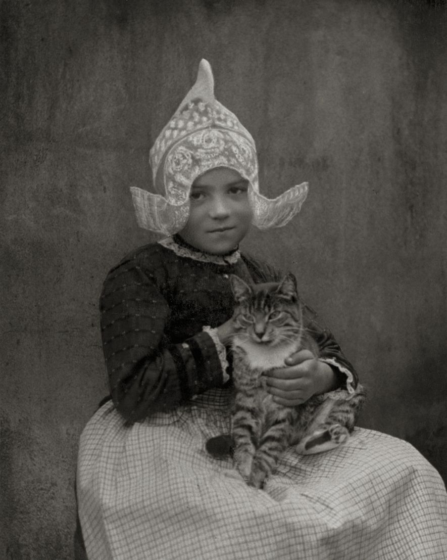 A young girl in 1920s Volendam, Netherlands, cradles a cat in her arms as she looks ...