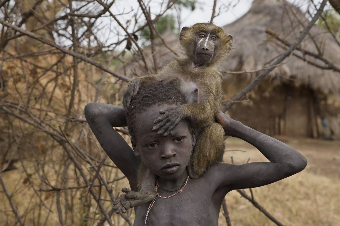 An Ethiopian boy and his pet baboon keep each other company in the Suri village of ...