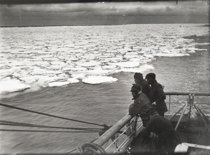 Crewmen observe pancake ice from the deck of the Terra Nova in December 1910, during Robert ...
