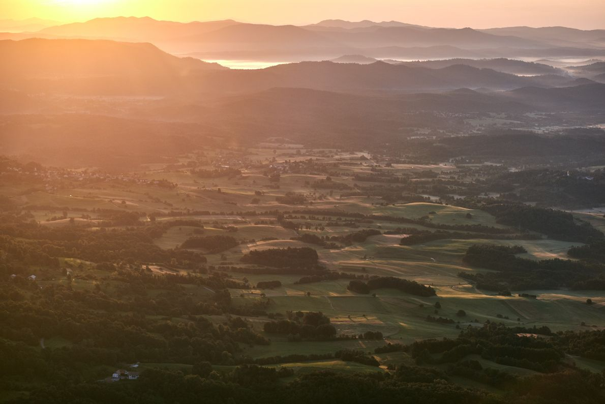 Golden hour. The sun sits low over the horizon, bathing the Vipava Valley in its warm, ...