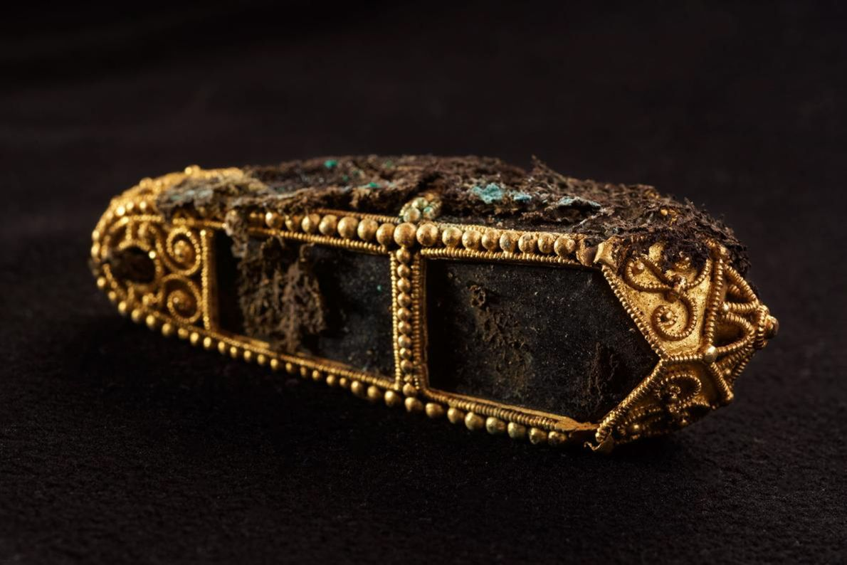 Still shrouded in bits of protective cloth, a gold pendant may once have contained a saintly ...