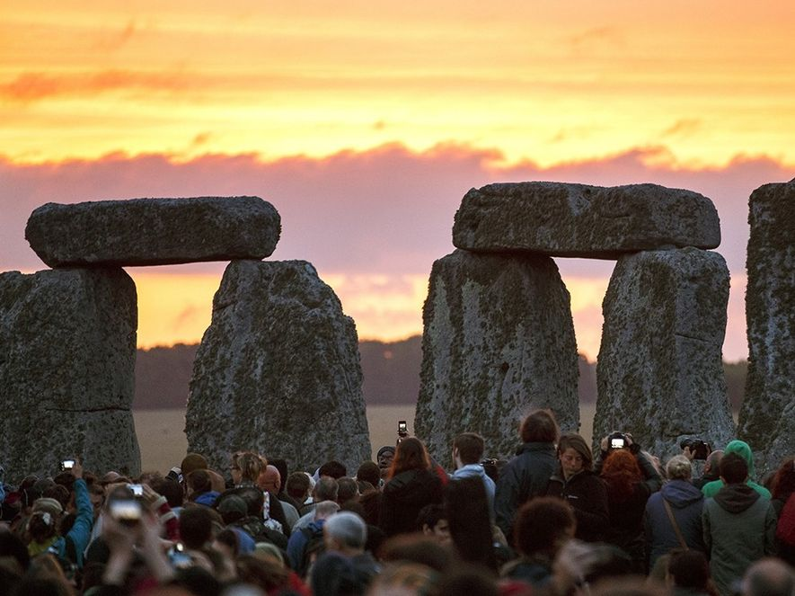 Revellers gather to observe the summer solstice sunrise. Thousands flock annually to the site to welcome ...