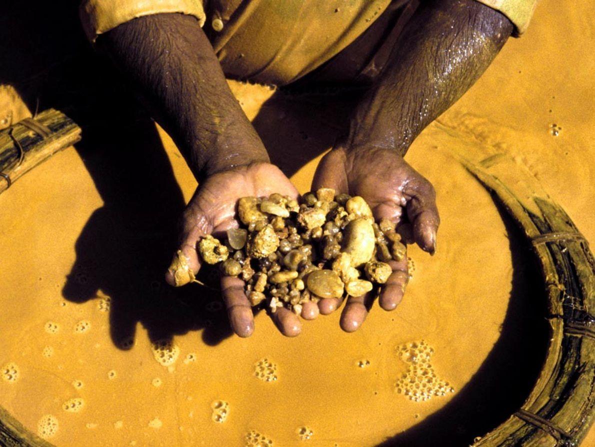 Awash in yellow, a gem miner near Ratnapura, Sri Lanka, separates stones from clay-laden mud. Local ...