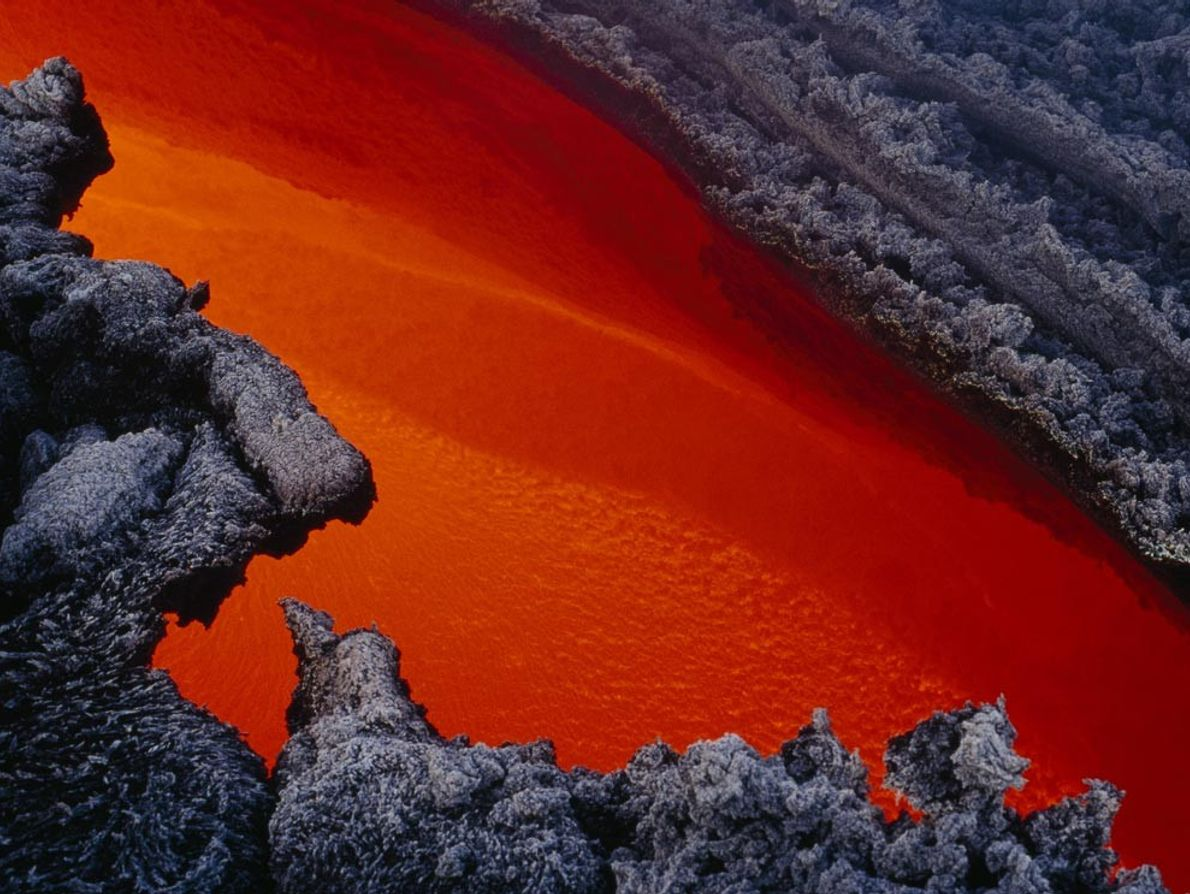 A river of molten lava flows through a channel in hardened lava after an eruption at ...
