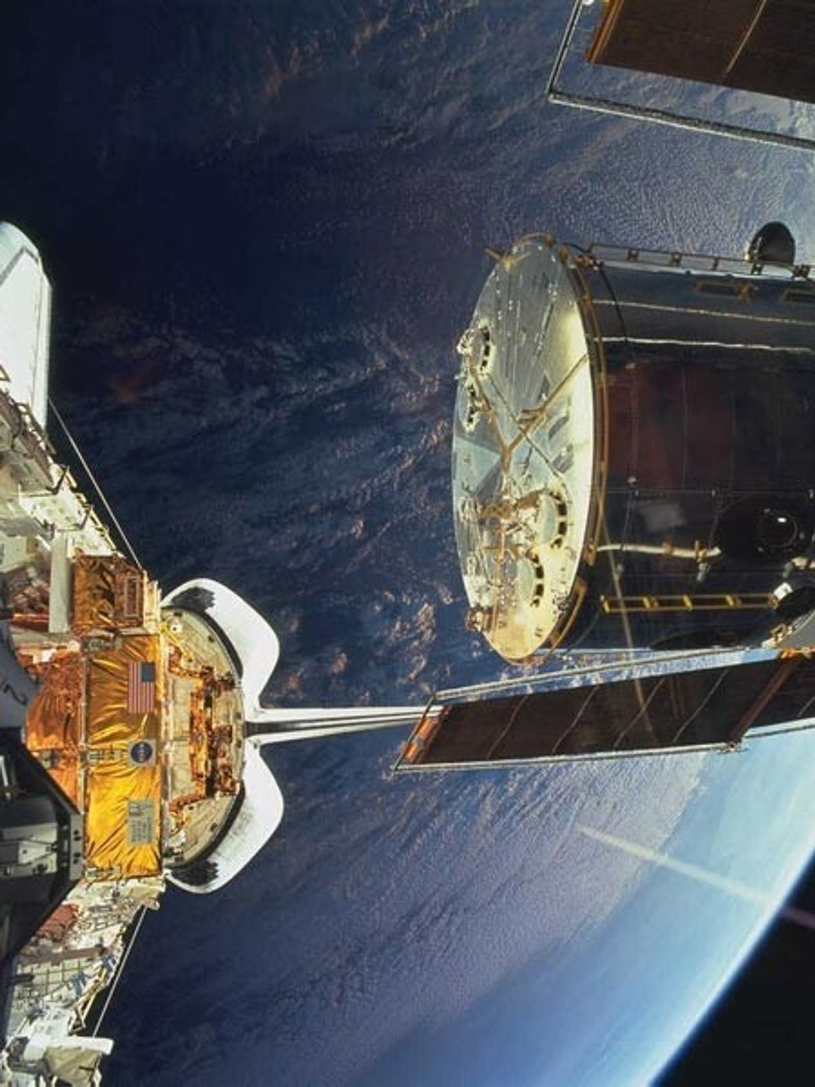 The Hubble telescope drifts back into space with Earth as its backdrop on Christmas Day 1999 ...