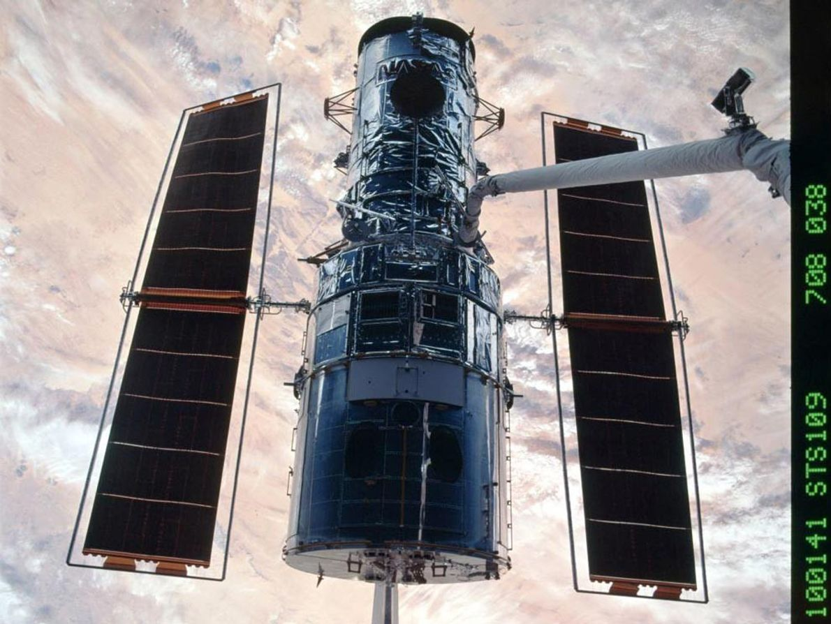 Space shuttle Columbia and the Hubble Space Telescope drift 360 miles (579 kilometers) over the Earth's ...