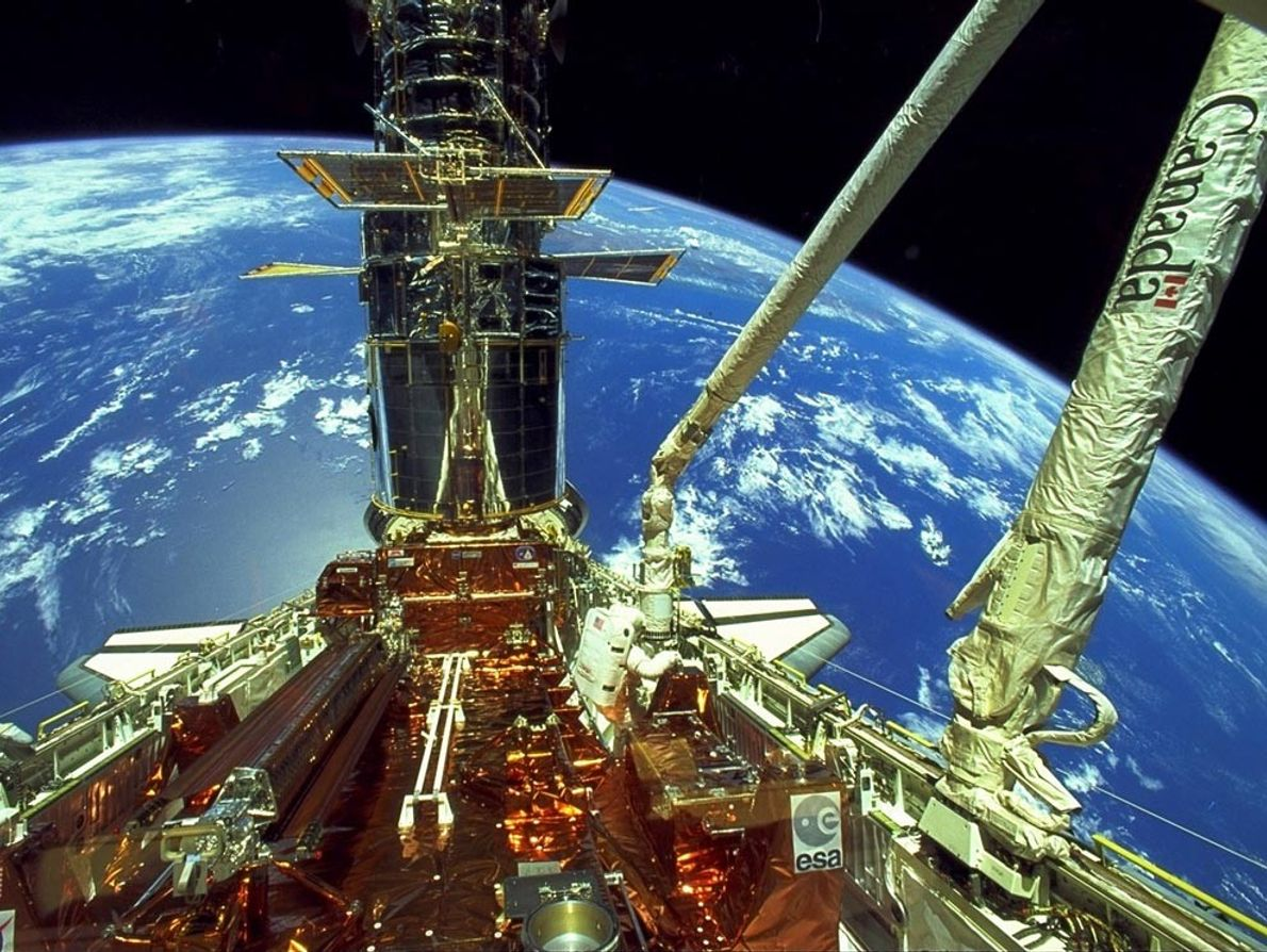 Astronaut Story Musgrave moves through space shuttle Endeavour's cargo bay (center) during deployment of the Hubble ...