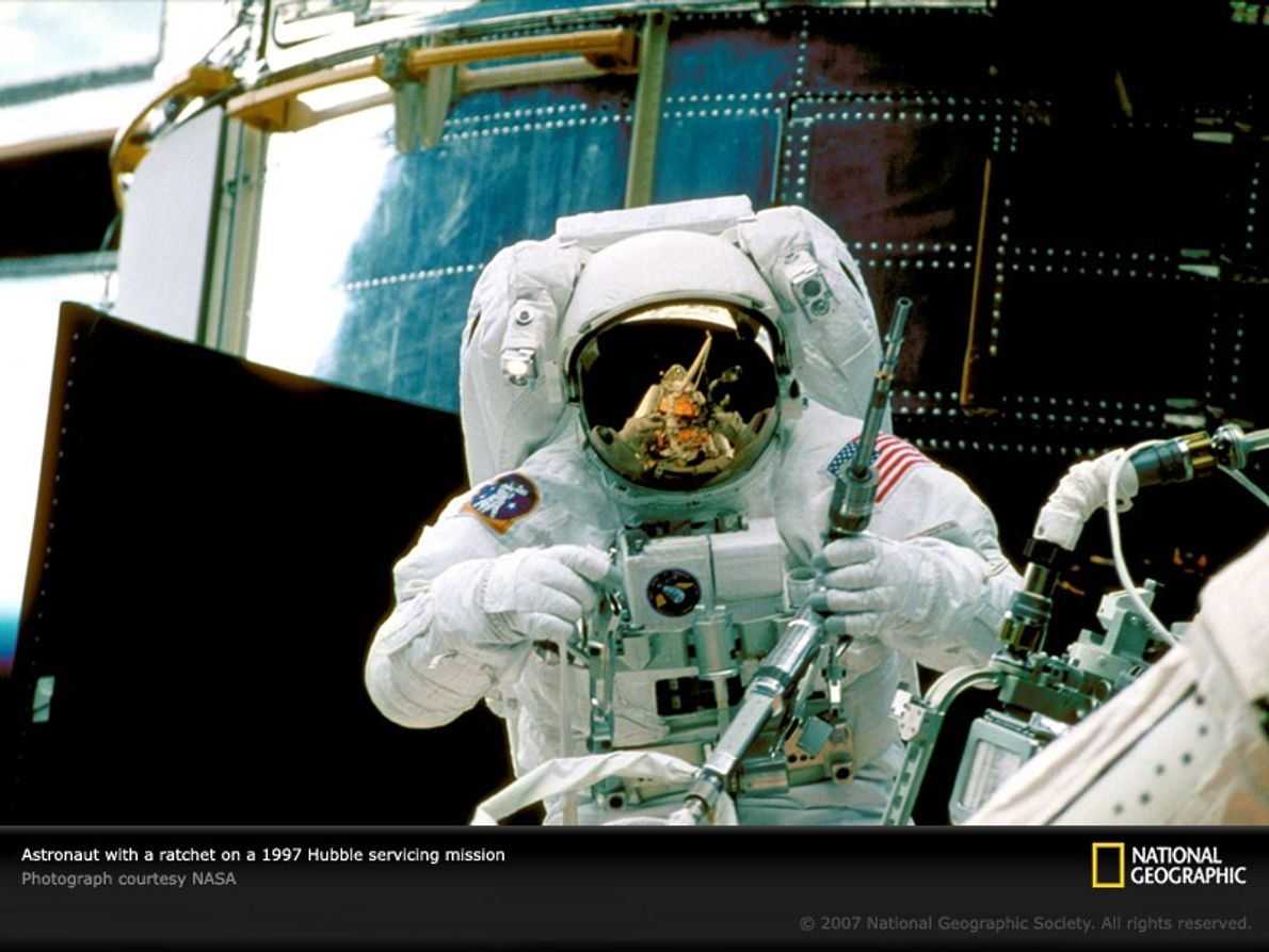 With the Hubble Space Telescope looming behind him, astronaut Steve Smith prepares to use a specially ...