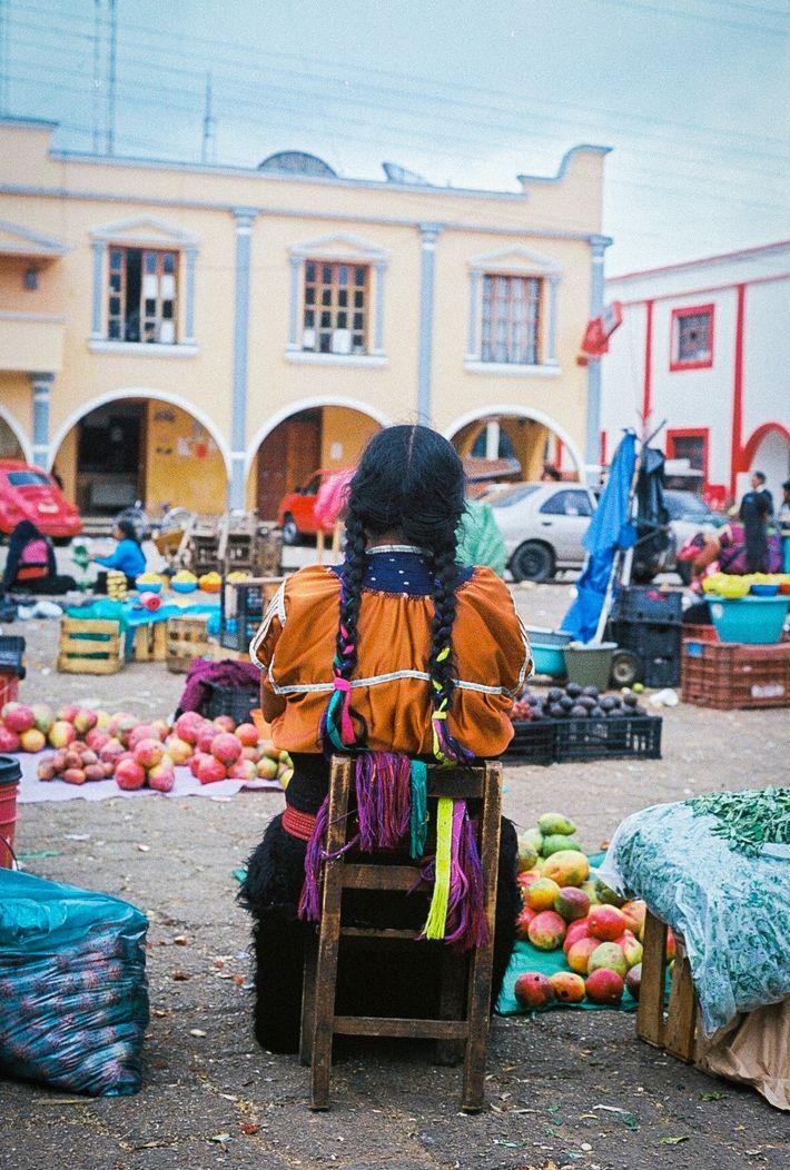 A woman sits at Mercado de Artesanias la Ciudadela