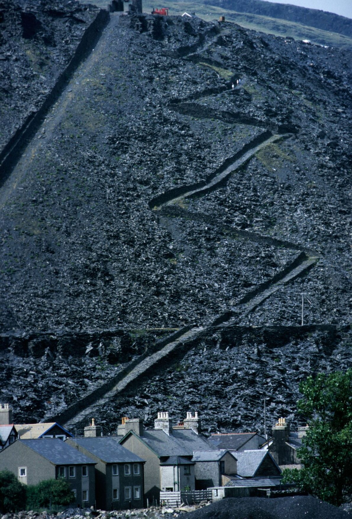 Spoil heaps with maintenance tracks tower above houses in Blaenau Ffestiniog. Most of the mines have ...