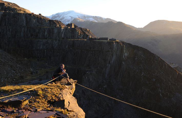 A climber rests atop an old quarry, Llanberis. Many of the former slate workings have been ...