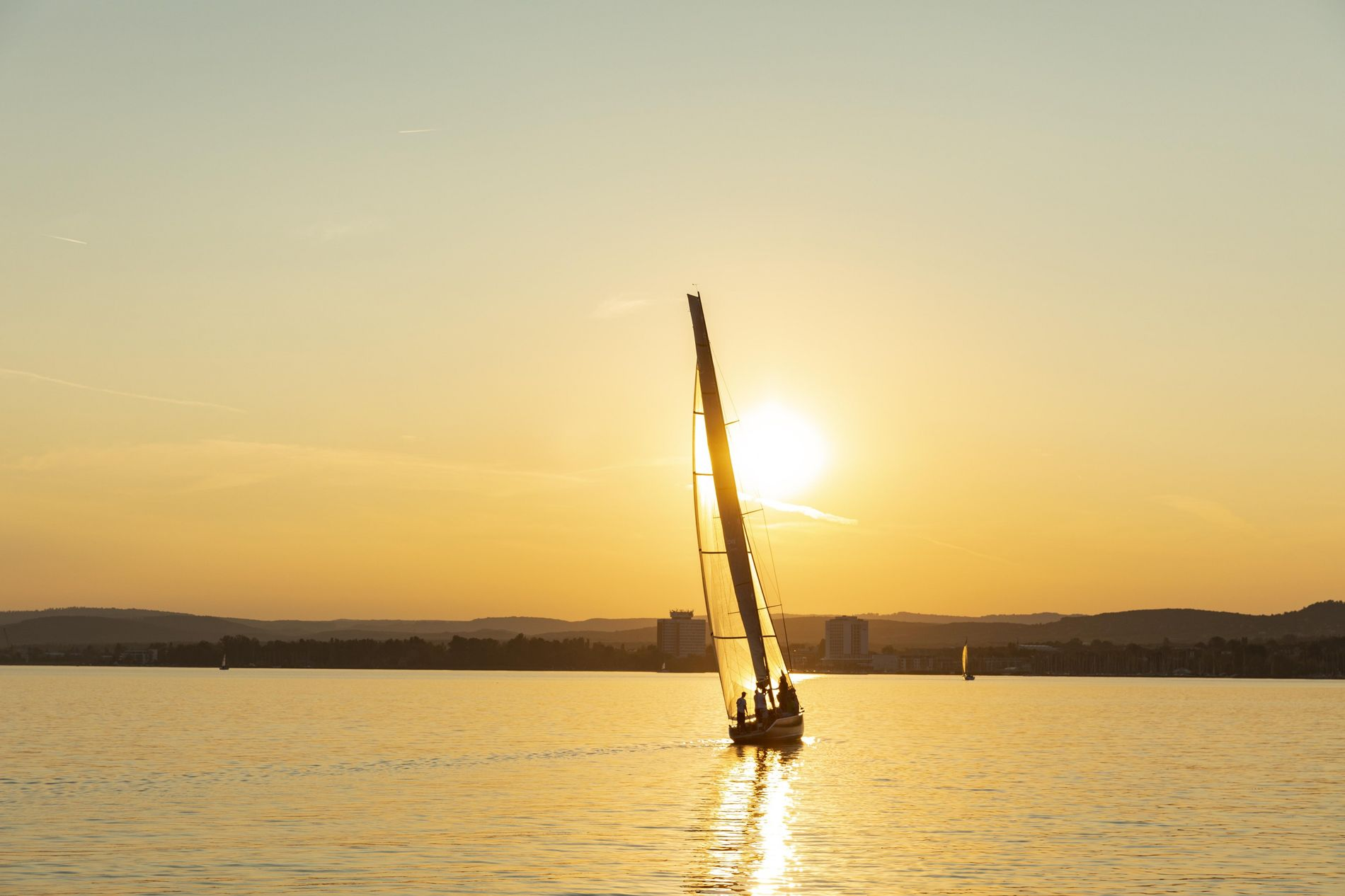 A sole sailboat glides on Lake Balaton, central Europe's largest lake, where Hungarians flock for fun ...