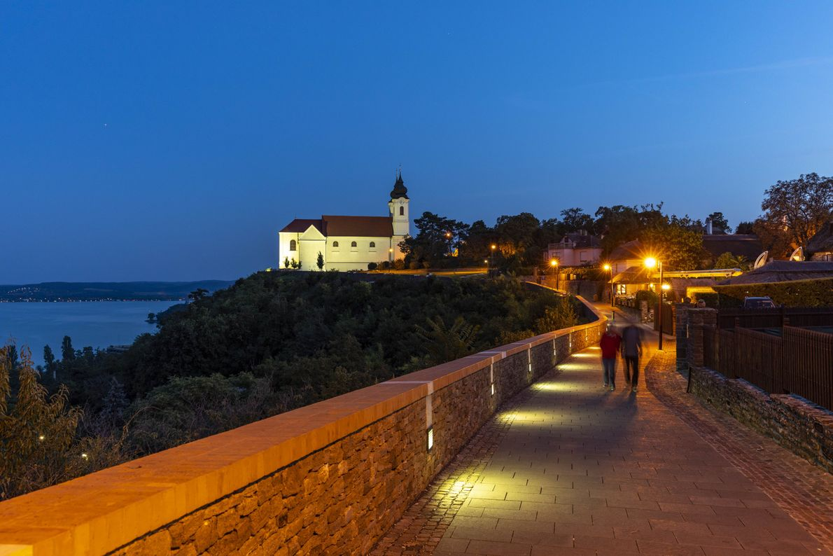 The glowing Benedictine Abbey lights the way at dusk on the Tihany Peninsula. The peninsula is ...