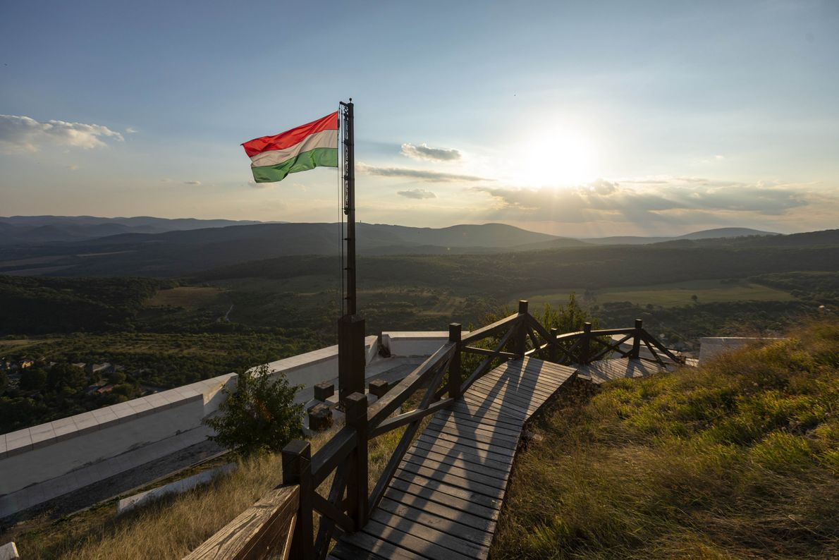 As the sun sets, the Hungarian flag flies from a pathway leading up to Füzér Castle. ...