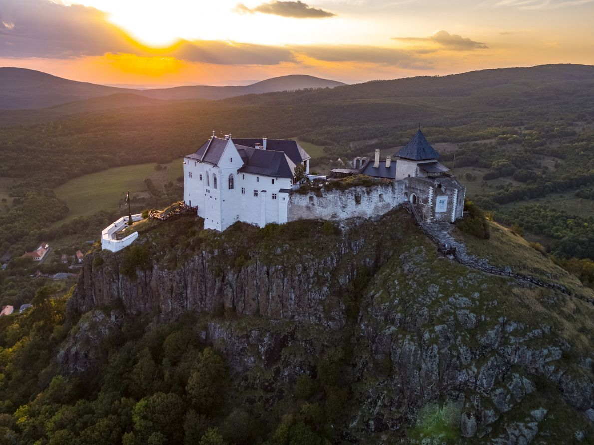 Sunset at Füzér Castle, a well-preserved medieval walled castle perched on a rocky hill above a ...